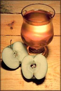 Fresh apple juice and an apple cut in half
