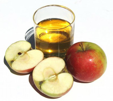 Apple juice is considered the most efficient kind of juice in cleansing your liver: picture of a glass of apple juice with two apples.