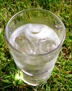 Drinking plenty of water is the natural non-radical way of doing a mild liver flush. Picture of a glass of water on grass.
